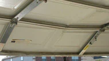 "alt="" a bent garage door that requires a door strut to straighten the door out"""