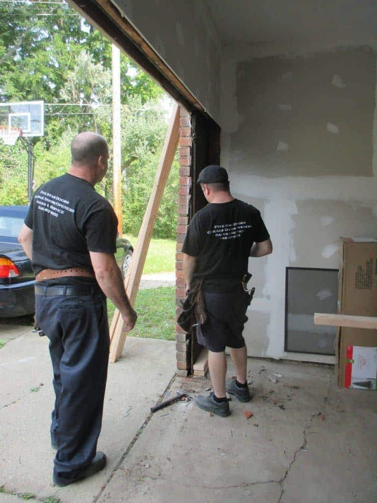 """alt=""""Shane and Andrew working on a garage door in South Lyon, Michigan"""""""